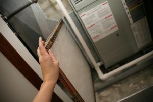 Person Replacing a Furnace Filter in Home